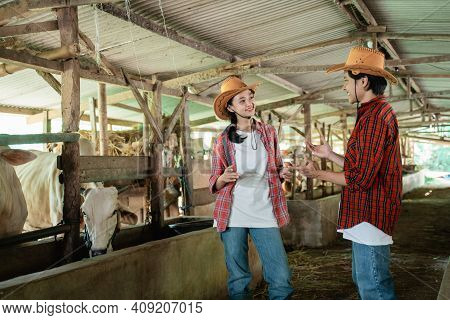 Two Cow Breeders Wearing Cowboy Hats Stand Chatting With Hand Gestures