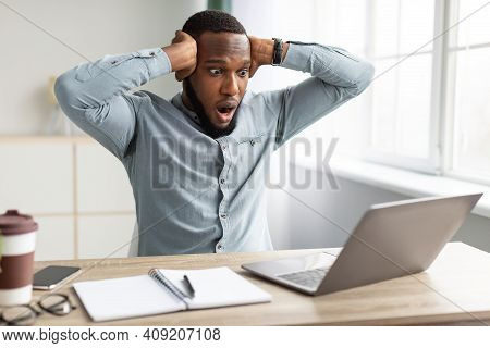 Oops, Problem At Workplace. Shocked African Businessman Looking At Laptop Computer Having Issue Work