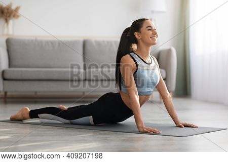 Active Young Woman In Sportswear Practicing Yoga At Home, Laying On Fitness Mat In Living Room And S