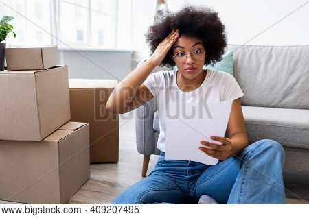 Large Expenses. Shocked Black Lady Reading Bill Sitting Among Moving Boxes In New Home. Renting Apar