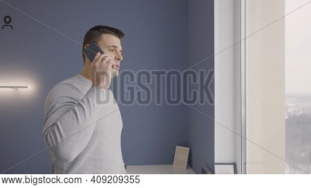 Man Is Talking On Phone Standing At Window. Action. Usual Conversation On Phone Of Man. Man At Home