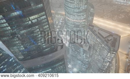 Skyscrapers In Snowfall At Night. Action. Top View Of Business High-rises With Beautiful Night Light