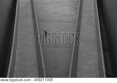 Overhead View Of Business Woman Walking Alone In Futuristic Looking Area In A City.