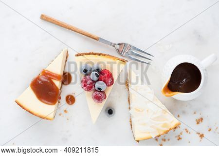 Cheesecake Slices With Various Toppings Top View. Caramel Sauce, Coconut And Frozen Berry Cheesecake