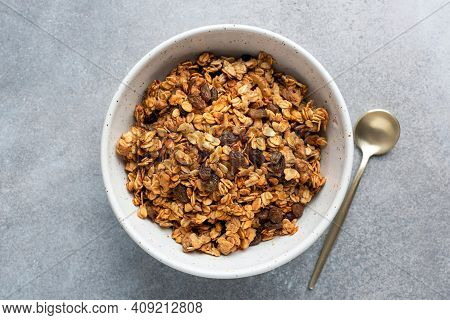 Homemade Oat Raisin Granola In Bowl On Grey Concrete Background, Top View. Healthy Breakfast Cereals