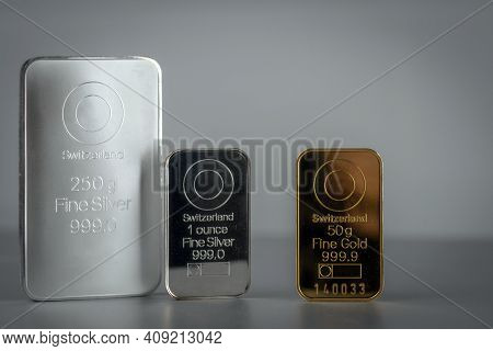 Gold And Silver Bars Various Weight Against A Grey Background.