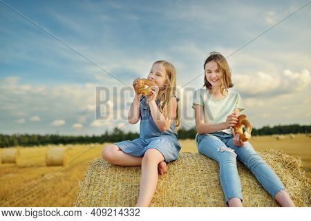 Adorable Young Sisters Eating Pretzels In A Wheat Field On A Summer Day. Children Playing At Hay Bal