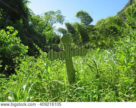 Lonely Stone Cross Amongst Caribbean Vegetation Under Tropical Blue Skies Of The French West Indies.