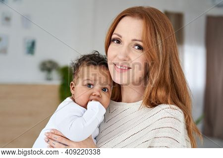Happy Young Caucasian Mother Holding Cute African American Baby Girl Looking At Camera. Diverse Mum
