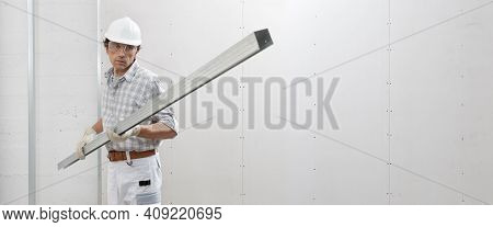 Man Worker With Drywall Metal Profile For Installing Plasterboard Sheet To Wall. Wearing White Hardh
