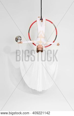 Little Acrobat Girl Shows An Acrobatic Performance With Mirror Ball On An Aerial Hoop