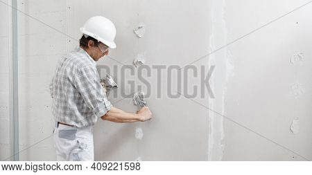 Man Drywall Worker Or Plasterer Putting Plaster On Plasterboard Wall Using A Trowel And A Spatula, F