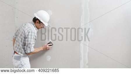 Man Drywall Worker Or Plasterer Sanding And Smoothing A Plasterboard Walls With Stucco Using A Sandp