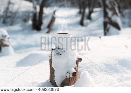 An Enamelled Mug With A Hot Drink Standing On A Snow-covered Stump In A Winter Forest. Steam Rises F