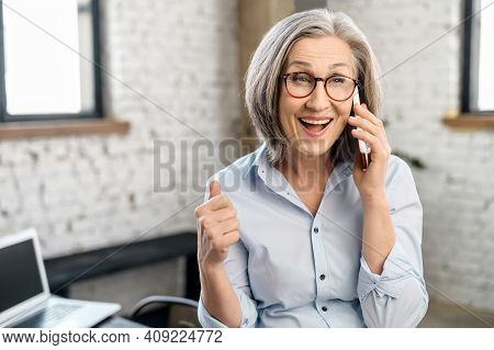 Excited Modern Mature Businesswoman In Glasses Standing In The Office, Taking Break To Call And Talk