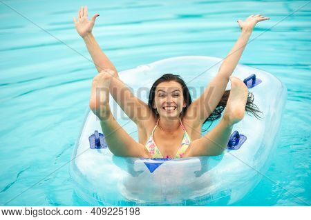 A Woman In A Bikini With A Rubber Inflatable Circle Playing And Having A Good Time In The Amusement
