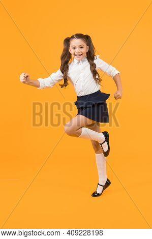 She Is Dynamic. Happy Energetic Schoolchild In Motion On Yellow Background. Little Girl With Long Ha