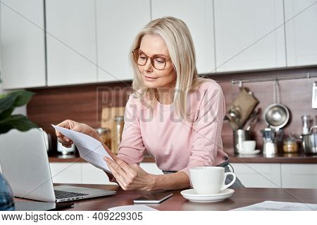 Middle Aged Older Woman Housewife Reading Paper Letter Or Bill Sitting In Kitchen At Home Office, Ch