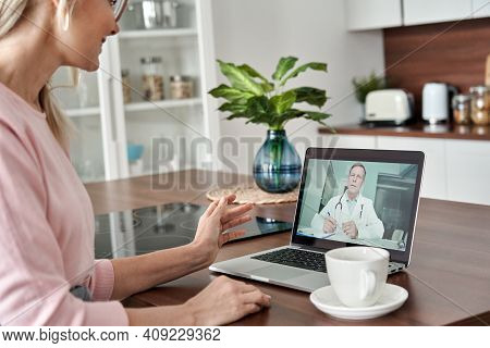 Middle Aged Female Patient Getting Online Telemedicine Consultation At Home. Male Doctor Consulting