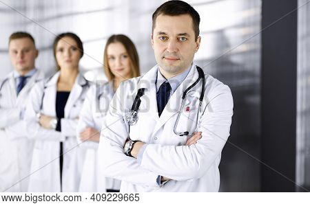 Group Of Professional Doctors, Standing As A Team With Crossed Arms In A Hospital Office, Ready To H