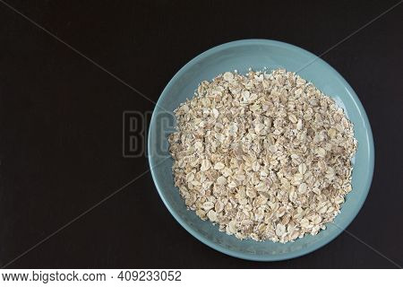 Flakes Of Oatmeal In A Turquoise Plate On A Dark Background, Healthy Breakfast, Hercules