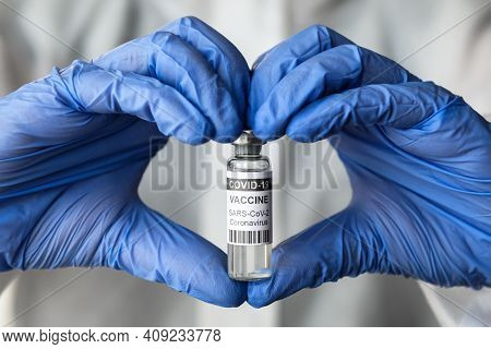 Covid-19 Vaccine In Doctor Hands With Heart Shape, Physician Holds Bottle Of Coronavirus Vaccine And