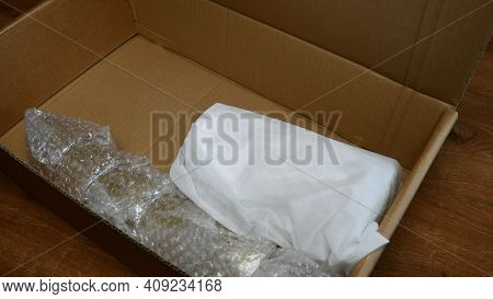 Fragile Tableware Packed Up Into Wrapping Bubble Plastic And Put Into Cardboard Box In Preparation T