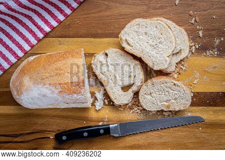 Freshly Baked Italian Bread, Sliced With A Serrated Bread Knife On A Wooden Cutting Board With A Red