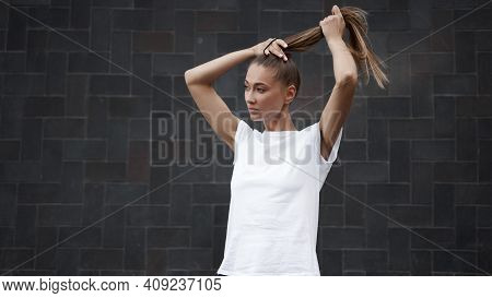 Woman Ties Her Hair In A Ponytail Before Morning Workout Black Wall Background. Young Athletic Femal