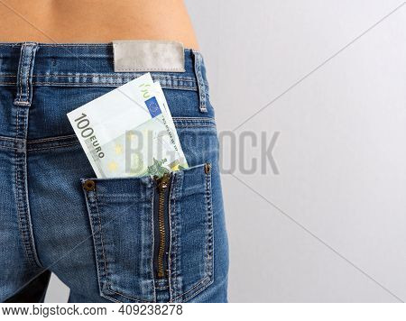 A Wad Of Hundred-euro Bills Protrudes From The Back Pocket Of Women's Jeans. Horizontal Photo. Money