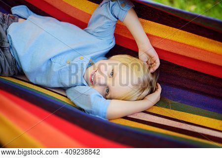 Cute Little Blond Caucasian Boy Having Fun With Multicolored Hammock In Backyard Or Outdoor Playgrou