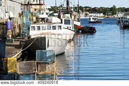 Lobster Fishing Boats Docked Behind Stores In A Canal In Porland Maine With Lobster Traps And Fishin