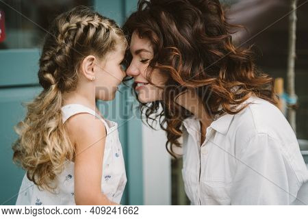 Portrait Of Little Daughter Kissing Her Beautiful Happy Mother