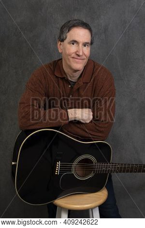 Male Musician With Arms Folded And Leaning On Guitar That Is On Its Side Atop Stool