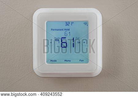 Photograph Of A Modern Residential Programmable Heating And Cooling Thermostat Mounted On A Wall