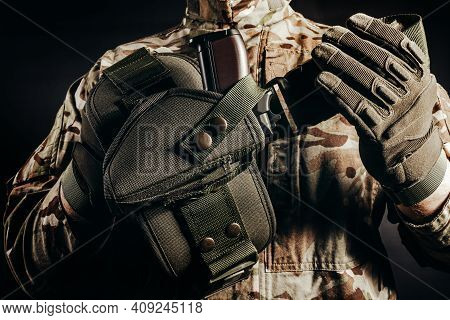 Photo Of Soldier In Camouflaged Uniform And Tactical Gloves Holding Gun Holster On Black Background.