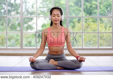 Asian Woman Practice Yoga Meditation Exercise  With Headphones At Home, Young Asia Female Sitting On