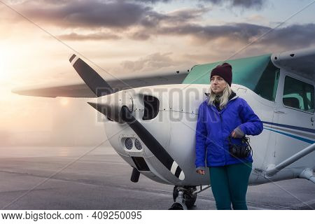 Young Caucasian Girl Student Pilot Is Standing In Front Of A Single Engine Airplane At The Airport.