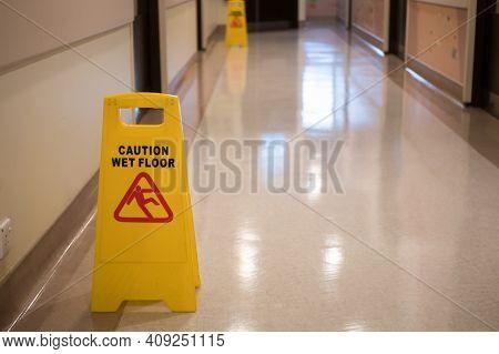 Sign Showing Warning Of Caution Wet Floor In Hospital Corridor.