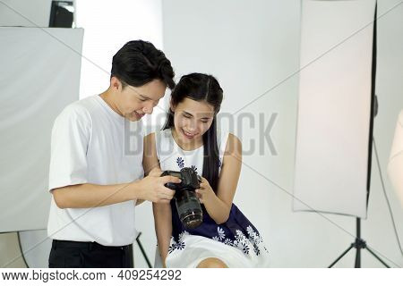 Asian Photographer Allow Model To View Picture Taken On The Camera Screen. The Young Model Is Very S