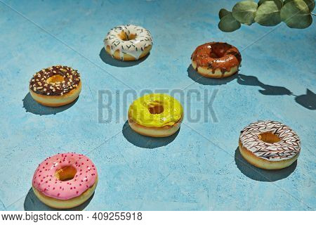 Multicolored Donuts With Frosting, Sprinkles And Leaves On Blue Background