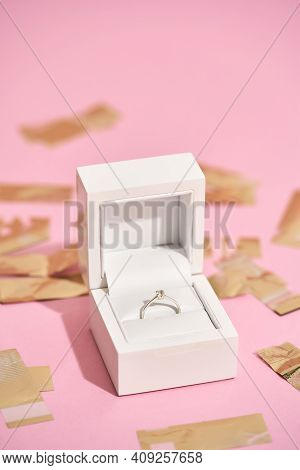 Be My Wife. Vertical Shot Of Elegant Engagement Diamond Ring In White Gift Box And Shiny Golden Conf