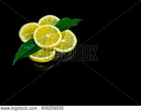 Slices Of Citrus Fruit Yellow Lemon With Green Leaves On A Black Background. Citrus Fruits Of Lemon.