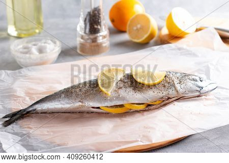 Mackerel Fishes Ready For Cooking Decorated With Lemon Slices, Spices On The Table. Cooking Mackerel