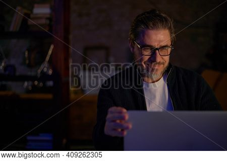 Older man working online with laptop computer at home sitting at desk. Home office, browsing internet, study room. Portrait of mature age, middle age, mid adult man in 50s.