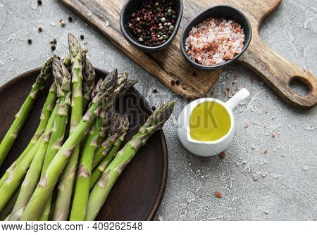 Bunch Of Raw Asparagus Stems With Different Spices And Ingredients On Grey Concrete Background. Top