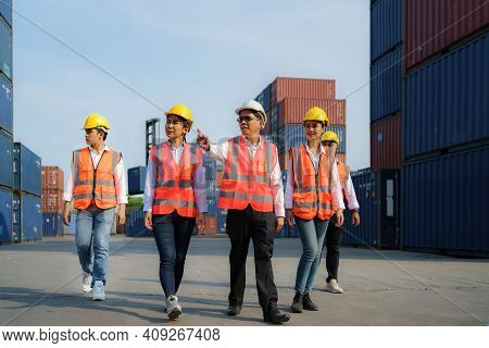 Asian Foreman Walking And Explaining The Various Operations In The Container Depot Terminal With Fou
