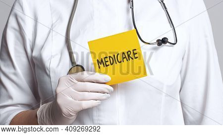 Cropped View Of Doctor In A White Coat And Sterile Gloves Holding A Note With Word - Medicare. Medic
