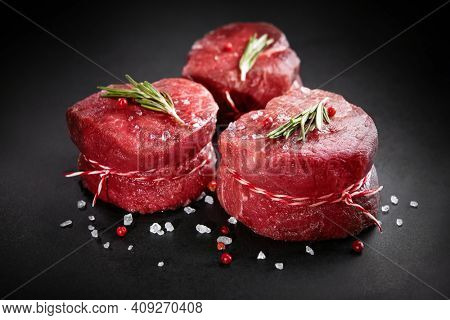 Raw beef filet mignon steaks with rosemary, pepper and salt on dark rustic board, black angus meat