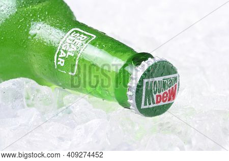 IRVINE, CALIFORNIA - OCTOBER 30, 2017: Bottle of Mountain Dew soda on ice. Mountain Dew citrus-flavored soft drink by PepsiCo. Mountain Dew was introduced in 1940.